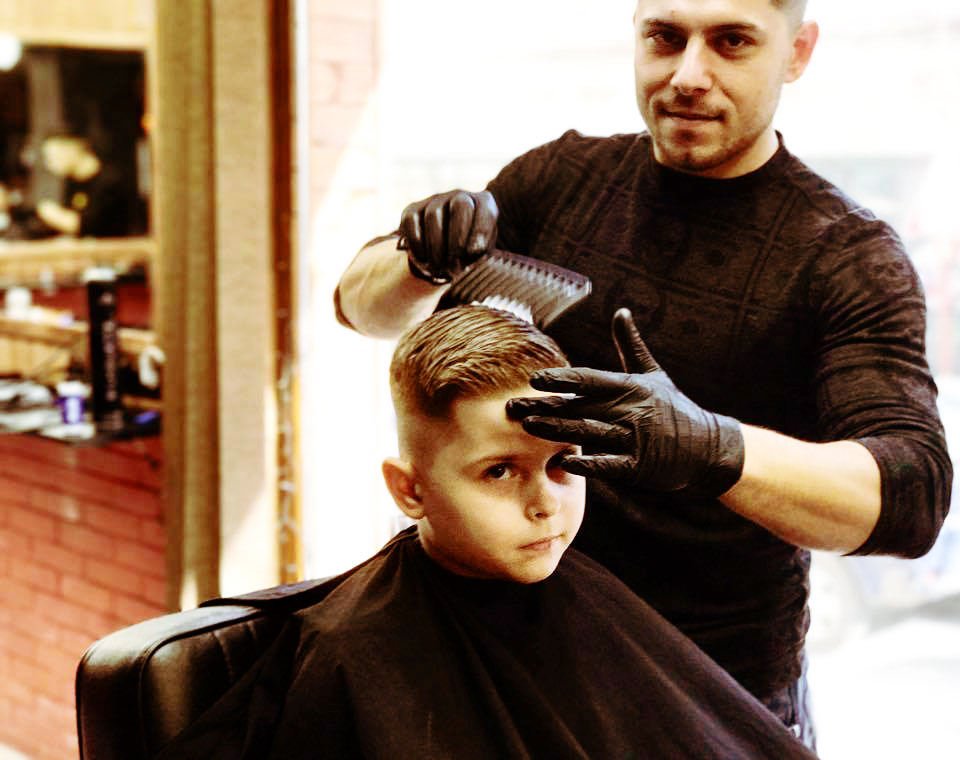 A child is getting a modern haircut at Bradao Barbershop in Varna Bulgaria
