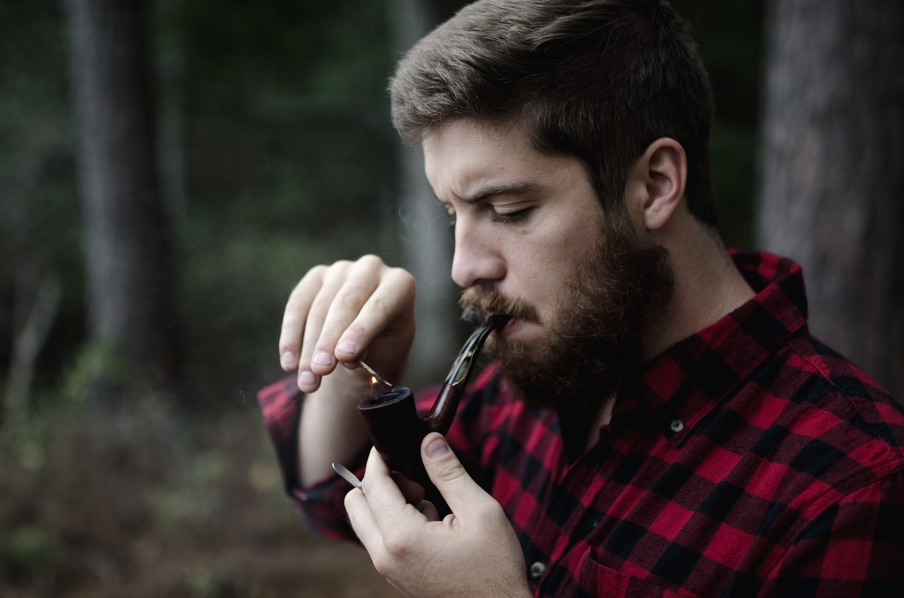 Man with beard and a pipe smoking